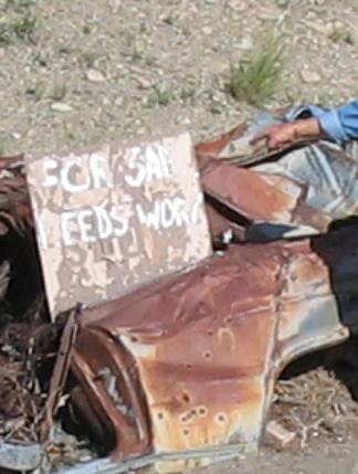 Frank Young with a For Sale Needs Work sign near Cerrillos, New Mexico